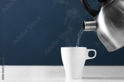 Pouring hot water into into a cup on a dark background. cup of tea with steam. metal kettle