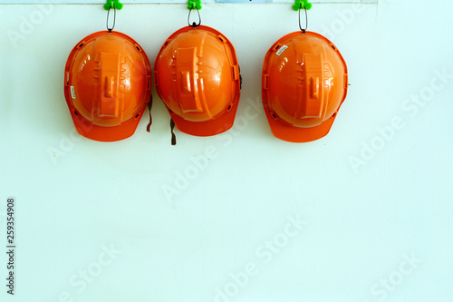 orange safety hat hanging on wall at the factory Canvas Print