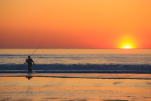 Beautiful Scene With Fisherman Silhouette With Rod Sitting On Sea Beach At Sunset