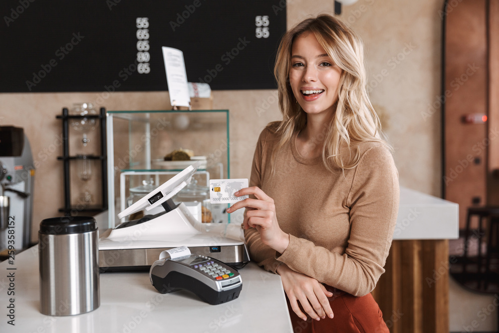 Fototapeta Girl happy excited buyer in cafe standing near terminal holding debit card.