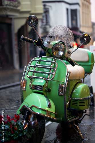 Cadres-photo bureau Motorise Green scooter through the rain parked on the street