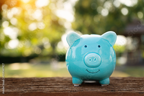 Cuadros en Lienzo Blue piggy bank on wooden table over blurred green bokeh background