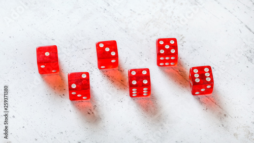 Photo  Six red translucent craps dices on white stone like board, showing all numbers f