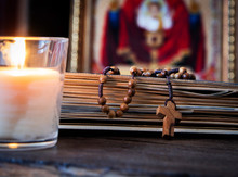 The Time For Prayer. Wooden Rosary On An Ancient Prayer Book. Icon Of The Mother Of God And Jesus. Lighted Candle