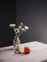 Eine Glastasse Mit Tee Neben Blumenvase Mit Anemonen Und Zitrone Auf Einem Keramikteller