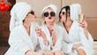 Leinwandbild Motiv Celebration party at spa. Friends congratulation. Young women with champagne. Sunglasses, bathrobes and turbans on.