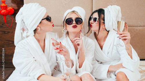 Celebration party at spa. Friends congratulation. Young women with champagne. Sunglasses, bathrobes and turbans on. - fototapety na wymiar