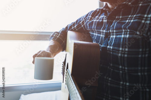 Fényképezés  men wearing a plaid shirt holding a coffee mug after playing the guitar