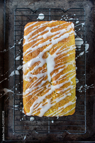 Photographie baked lemon poppy seed cake loaf with white icing drizzle flat lay