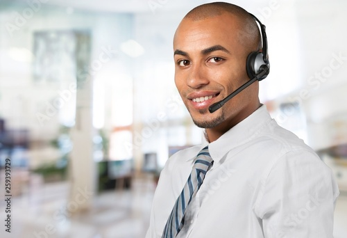Young male phone service manager on blurred office background
