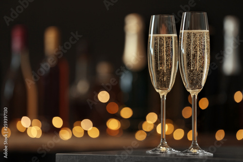 Canvas Print Glasses of champagne on table against blurred background