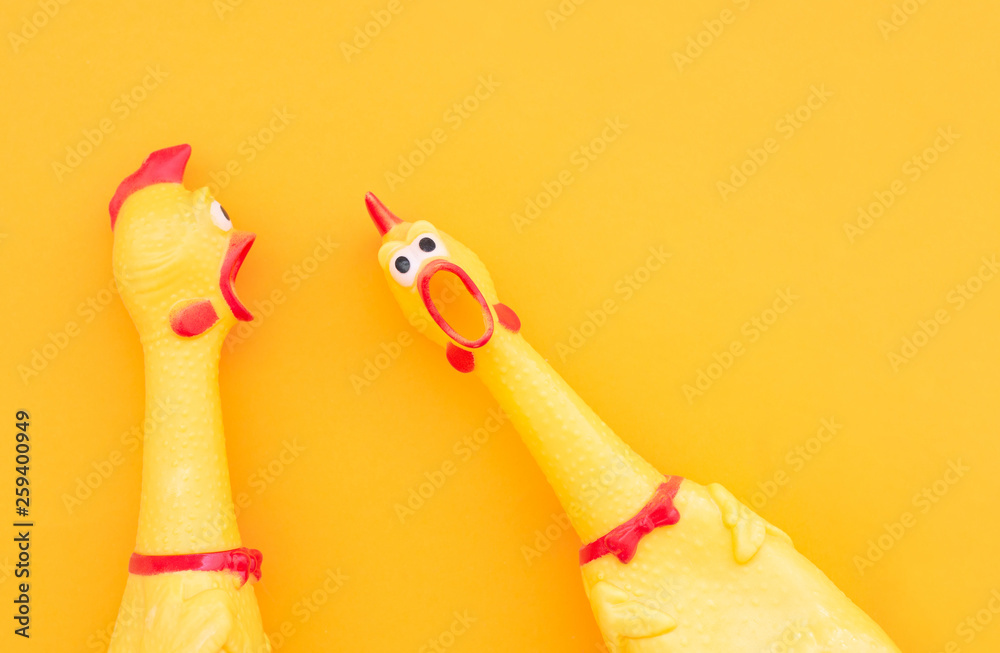 Fototapety, obrazy: Surprised chicken toys are isolated on a orange background, one looks at the camera and shouts, the other one to the side. Screaming chicken toys on a yellow background.