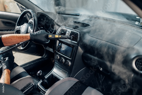 Carwash, worker cleans salon with steam cleaner Fototapet