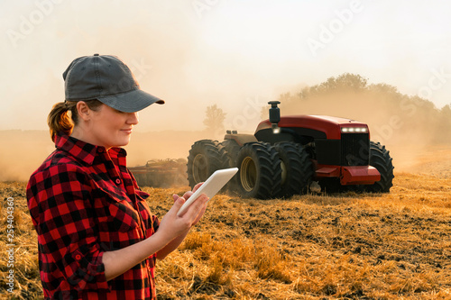 Aufkleber - Woman  farmer with digital tablet controls an autonomous tractor on a smart farm