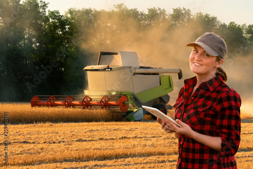 Aufkleber - Woman farmer uses a digital tablet control autonomous harvester. Smart farming concept