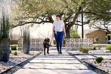 Smiling Woman With Dog Walking On Footpath