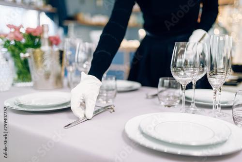 Obraz Waitress in gloves puts the knife, table setting - fototapety do salonu