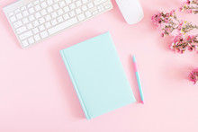Office Pink Table, Notepad, Keyboard, Flowers, Notebook, Stationery On Pink Background. Business Minimal Concept For Women. Flat Lay, Top View, Copy Space