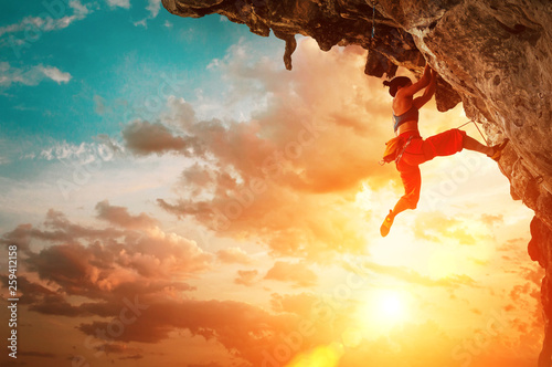 Fotografie, Obraz Athletic Woman climbing on overhanging cliff rock with sunset sky background