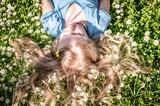 Fototapeta Zwierzęta - cute child lying in daisy meadow