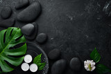 Fototapeta Kamienie - Zen stones and leaves with water drops. Spa background with spa accessories on a dark background. Top view. Free space for your text.