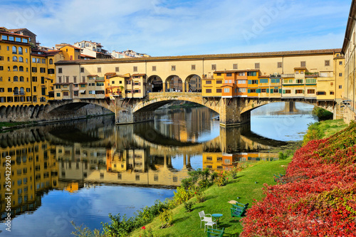 Garden Poster Old building View of the historic Ponte Vecchio with reflections in the Arno river during autumn, Florence, Tuscany, Italy