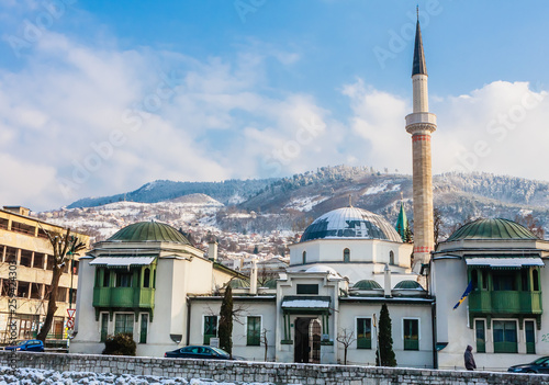 Fotografia  A minaret rises over buildings across the river from the Old Town neighborhood of Sarajevo