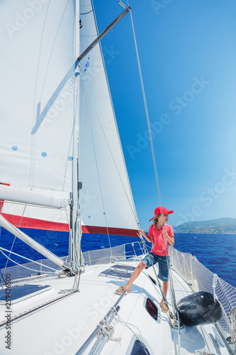 Staande foto Zeilen Little boy on board of sailing yacht on summer cruise. Travel adventure, yachting with child on family vacation.