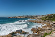 Sydney, Australia - February 11, 2019: Wide shot of Bronte beach with neighborhoods above and rocks to the north and south. Blue sea and blue sky. Waves crashing on rocks.