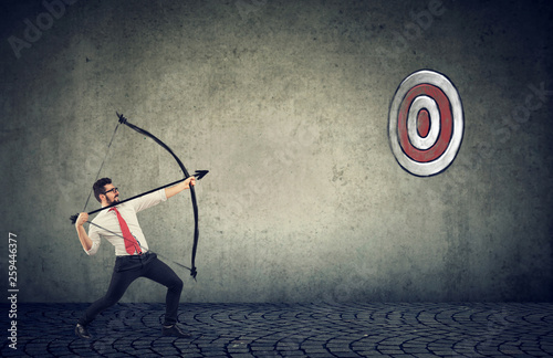 Foto auf Leinwand Akt business man trying to hit a target his goal with bow and arrow
