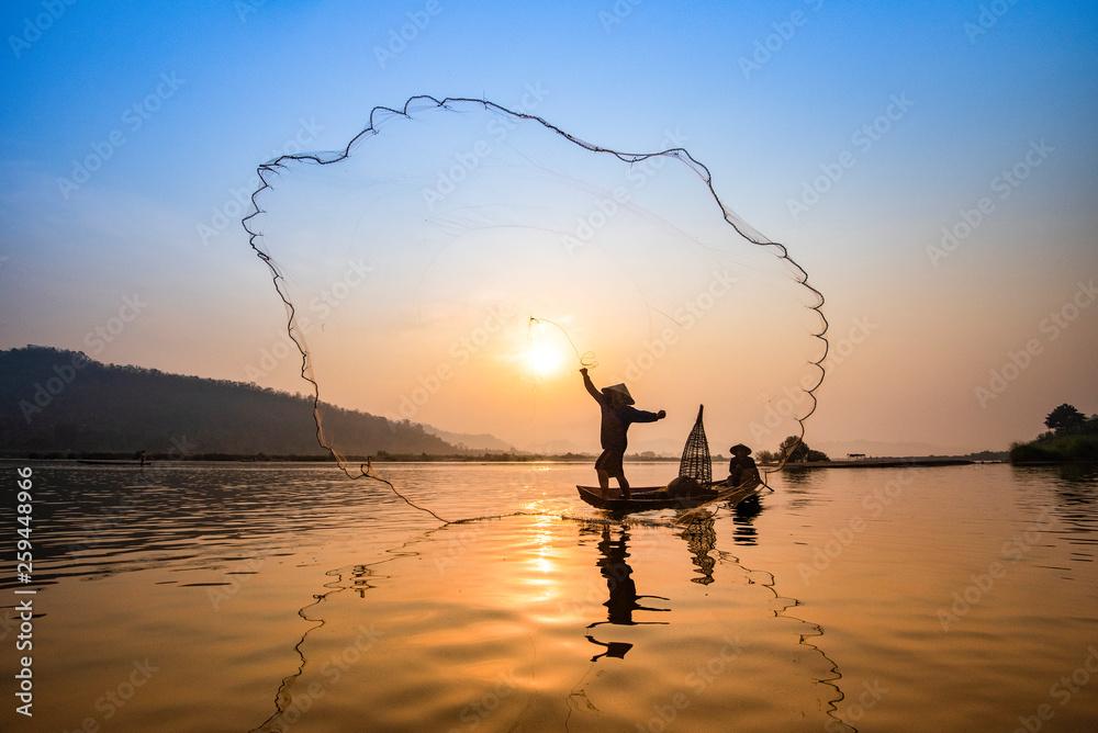 Fototapeta Asia fisherman net using on wooden boat casting net sunset or sunrise in the Mekong river