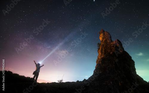 Obraz Man stand between rock mount and milky way - fototapety do salonu