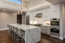 Beautiful Kitchen In New Luxury Home, With Tall Ceiling, Waterfall Island, Stainless Steel Appliances, And Hardwood Floors
