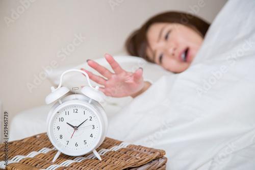 目覚まし時計で起きる女性(時計にピント) Fototapet