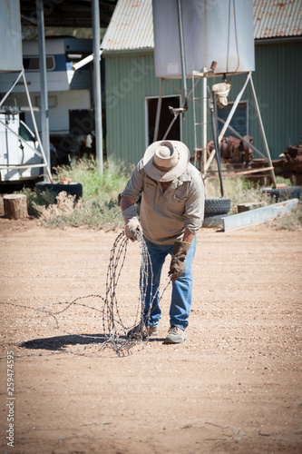 Farmer rolls a length of barbed wire with leather gloves on the property Canvas Print
