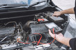 Services car engine machine concept, Automobile mechanic repairman hands repairing a car engine automotive workshop with a wrench and digital multimeter testing battery, car service and maintenance