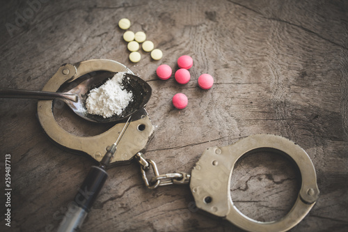 Drug syringe and cooked heroin on spoon and handcuffs Wallpaper Mural