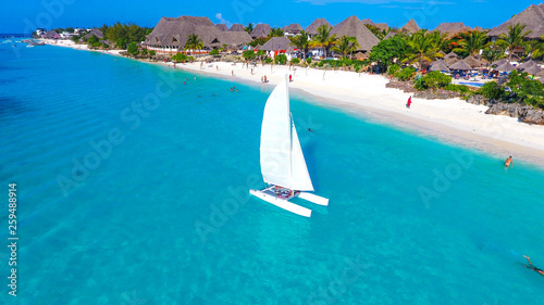Poster Zanzibar White sailboat in a sea of traditional Dhow Zanzibar Beach. Aerial view