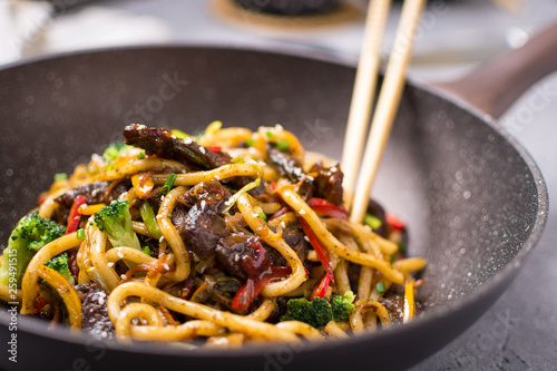 Udon Stir-Fry Noodles with Beef and Vegetables in Wok Pan on Dark Background Fototapeta