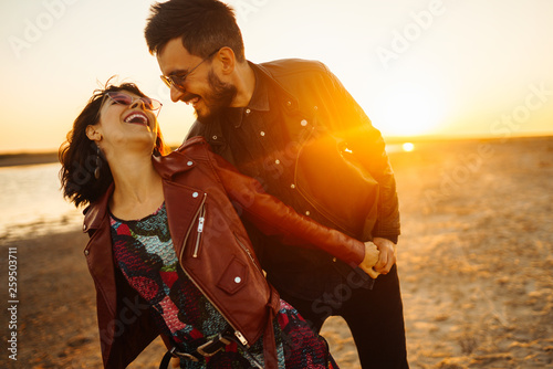 Obraz Enjoying time together.  Stylish and loving couple enjoying each other by the sea. The couple is young and in love. The concept of youth, love and lifestyle. Beautiful sunset on a summer day. - fototapety do salonu