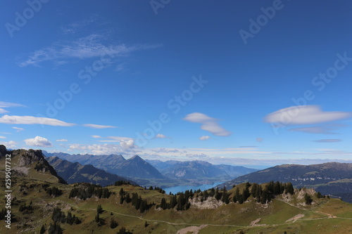 Fotografia  Scenic alpine Mountain View with green hills and lake.