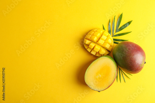 Photo Cut ripe mangoes and space for text on color background, top view