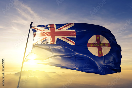 Fotografia  New South Wales state of Australia flag waving on the top sunrise mist fog