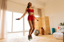 Woman Wearing Red Shorts And Sneakers Skipping The Rope At Home
