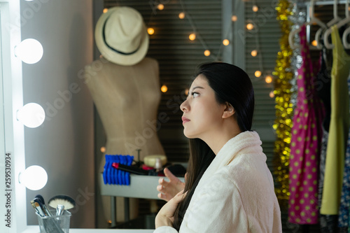 side view Young sassy asian woman wear bathrobe in dressing room face looking mirror with lights tidy up her hair hands soft touching brush by finger Fototapet