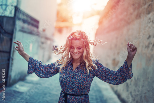 Fotografie, Obraz  Carefree happy woman dancing on moody narrow street in sunset