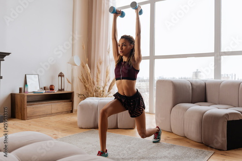 Photo Sportswoman lunging forward with blue barbells at home