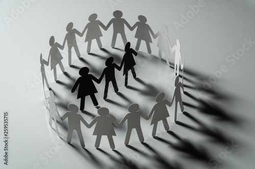 Photo Three human paper figures surrounded by circle of paper people holding hands on white surface