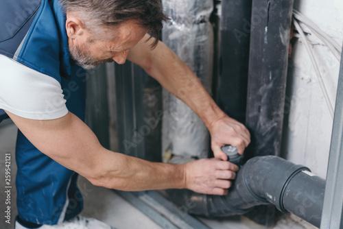 Fotografia  Handyman checking a plumbing connection