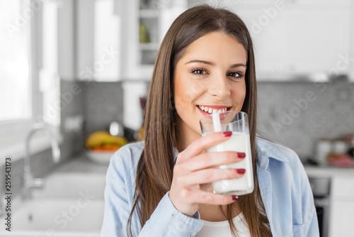 Obraz Close up of happy young woman drinking milk. - fototapety do salonu